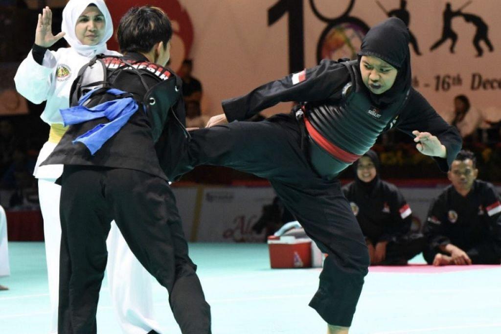TEPAT PADA SASARAN: Nur Syaza Insyirah Md Roslan (kanan) memberikan saingan yang sengit kepada pesilat Indonesia, Nimalasari Octaviani dalam pertarungan Kelas B yang dimenangi pesilat Singapura itu 3-2.