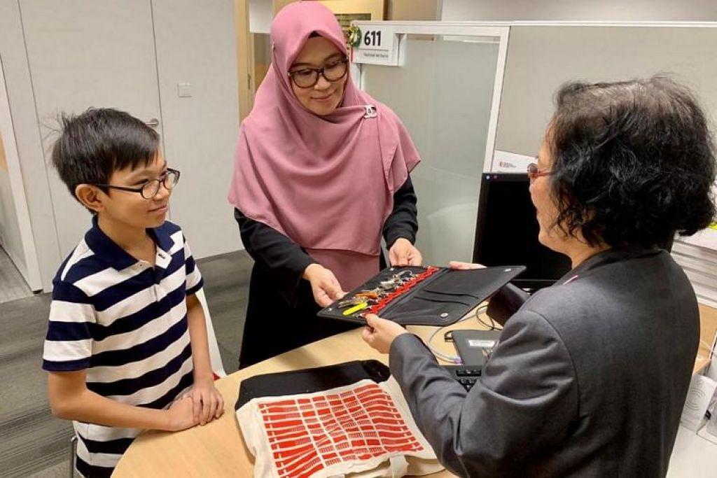 Cik Fazilah, ditemani anak lelakinya, mengambil kunci bagi rumah baru mereka di HDB Hub di Toa Payoh Khamis lalu.