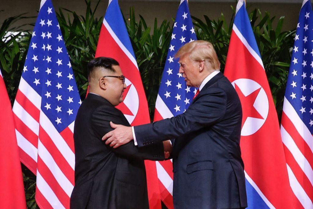 LAKAR SEJARAH: Presiden Amerika Syarikat Donald Trump (kanan) bersalaman dengan pemimpin Korea Utara Kim Jong Un di Hotel Capella, Sentosa Jun lalu. – Foto BH oleh KEVIN LIM