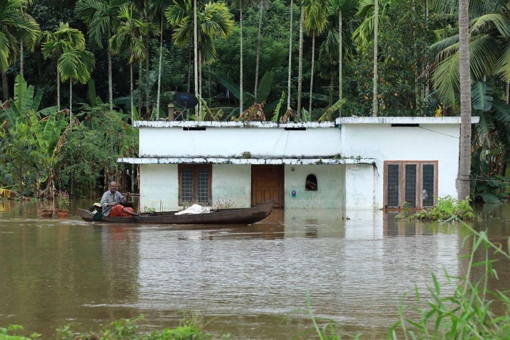 BANJIR TERBURUK DALAM 100 TAHUN: Seorang lagi berdayung mencari keselamatan sementara sebuah rumah hampir tenggelam sepenuhnya di daerah Ernakulam, Kochi, semasa negeri Kerala di India dilanda bah terburuknya dalam satu abad. – Foto fail AFP