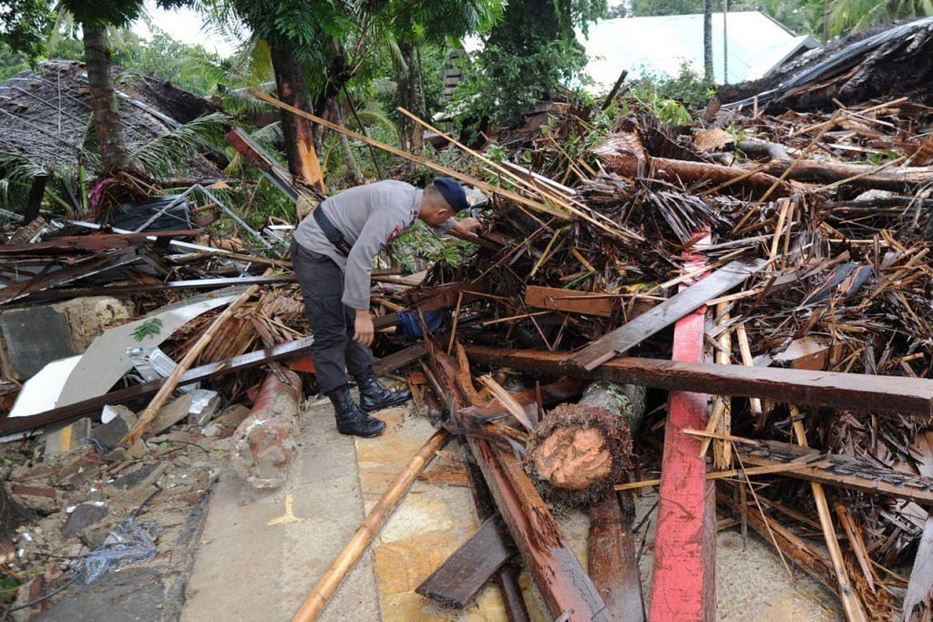 CARI MANGSA: Seorang anggota polis Indonesia mencari mangsa-mangsa di bawah runtuhan Mutiara Carita Cottages di Carita, Banten semalam. - Foto AFP