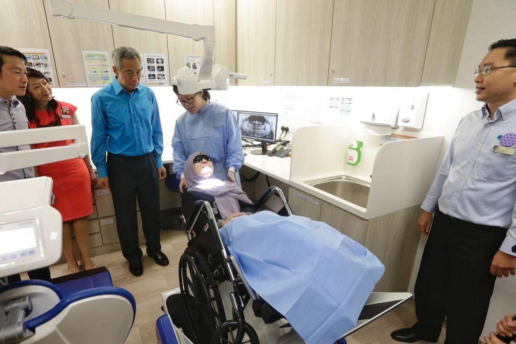 POLIKLINIK DIPERTINGKAT: Perdana Menteri Lee Hsien Loong (tiga dari kiri) yang ditemani (dari kiri) Menteri Negara Kanan (Kesihatan merangkap Pengangkutan), Dr Lam Pin Min; CEO NHGP Profesor Madya Chong Phui-Nah; serta Pengarah Perkhidmatan Dental NHGP Dr Kenneth Low (kanan) memerhatikan penggunaan penyondong kereta roda di Poliklinik Ang Mo Kio yang dipertingkat awal tahun ini. - Foto BH oleh KEVIN LIM