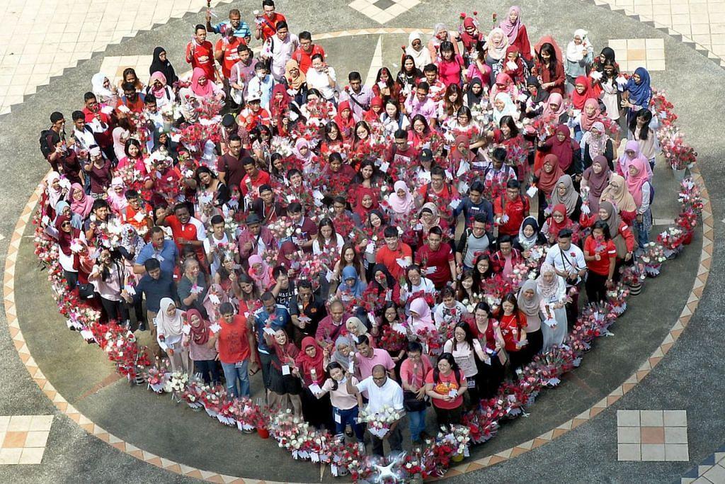 HARGAI KEHARMONIAN: Lebih 250 belia daripada pelbagai kaum, agama dan budaya berkumpul dengan sama-sama membahagi 7,000 kuntum bunga mawar di seluruh Singapura sebagai sebahagian daripada inisiatif silang agama yang diberi nama 'Roses of Peace - World Peace Starts With Me' yang diadakan pada 2016. - Foto fail