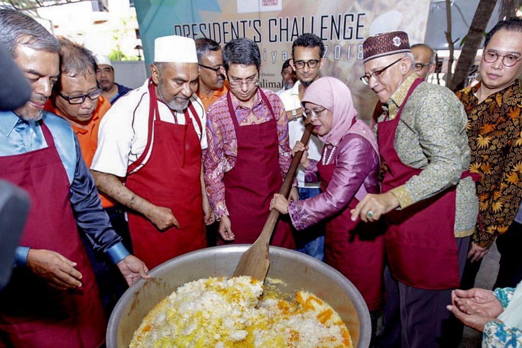 SENTUHAN PRESIDEN: Puan Halimah menggaul nasi beriani di dapur Masjid Khalid sempena acara beriani amal bagi Cabaran Presiden tahun lalu. – Foto fail