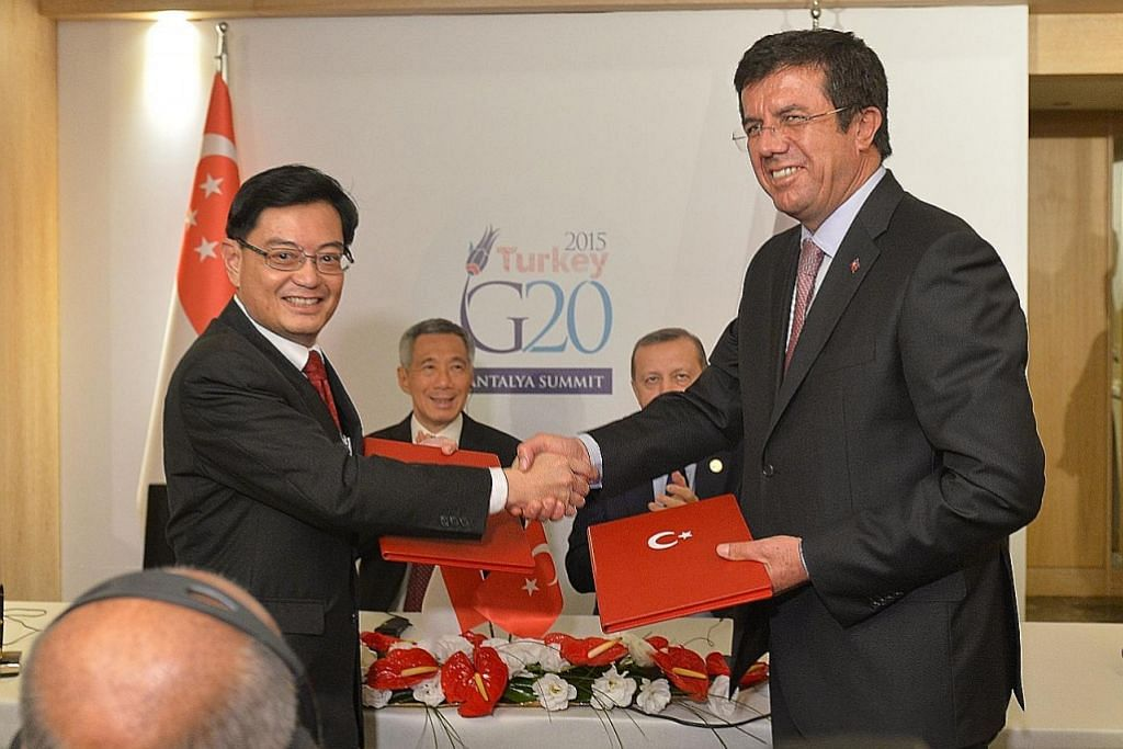 CAPAI PERSETUJUAN: Encik Heng berjabat tangan dengan rakan sejawatannya dari Turkey, Encik Nihat Zeybekci, semasa menemani Perdana Menteri Lee Hsien Loong ke Sidang Puncak Kumpulan 20 (G20) di Turkey pada 2015. - Foto fail