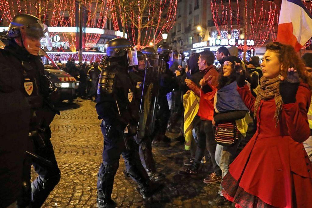 BANTAHAN DI PARIS - TERUS BANTAH: Lama selepas pertunjukan bunga api berakhir, bantahan baju kuning atau 'gilets jaunes' yang bermula tahun lalu berterusan di Champs-Elysees di Paris pada malam Tahun Baru. Pergerakan yang dimulakan bagi membantah kenaikan harga minyak dan kos sara hidup yang melambung itu didakwa pemerintahnya sebagai disalah guna sebahagian pihak untuk menjejas ekonomi negara itu.  - Foto AFP