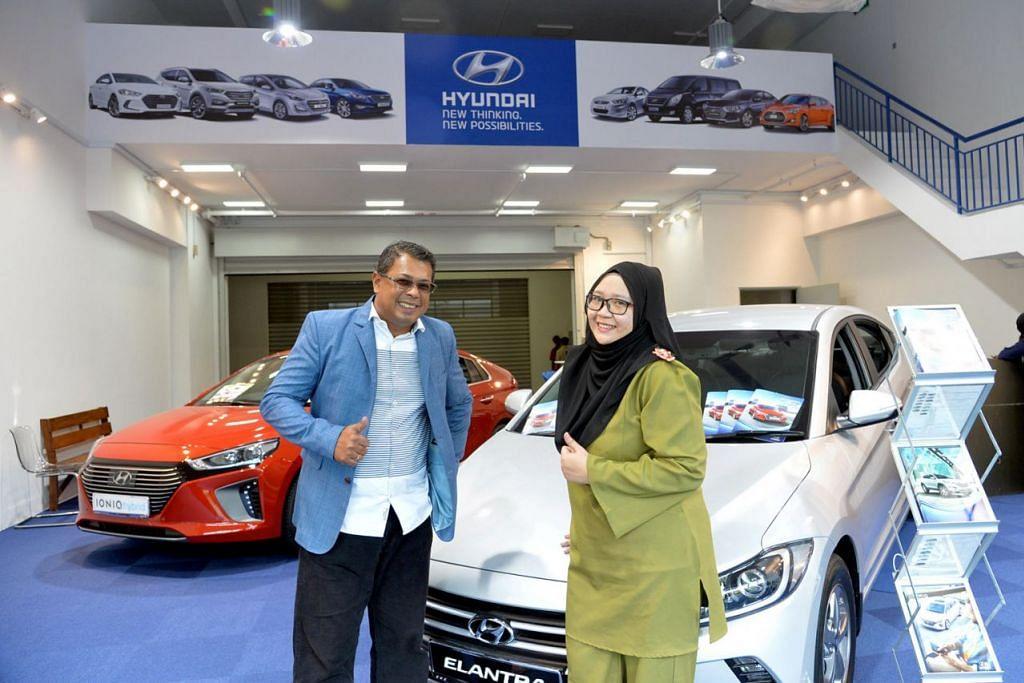 DI BILIK PAMERAN: Pemilik Doktor Kereta, Encik Ismail Yusof, bersama Cik Aisyah Amirah Abdul Rahman di bilik pameran kereta syarikat itu. - Foto fail