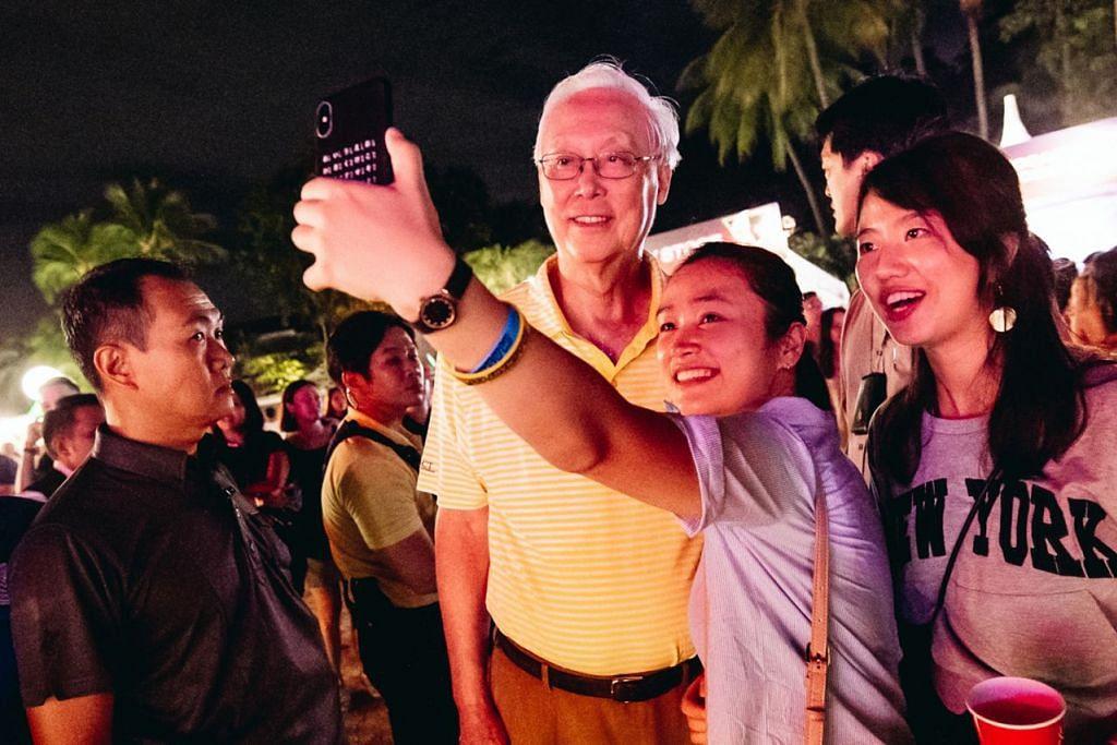 SWAFOTO DI SENTOSA - TURUT SERTA: Menteri Kanan Emeritus Goh Chok Tong (dua dari kiri) mengambil swafoto bersama dengan dua peserta pesta di Pantai Siloso di Sentosa kelmarin. Menurut penganjur, acara itu satu-satunya pesta pantai di Singapura yang dianjurkan bagi menyambut tahun baru. - Foto SENTOSA