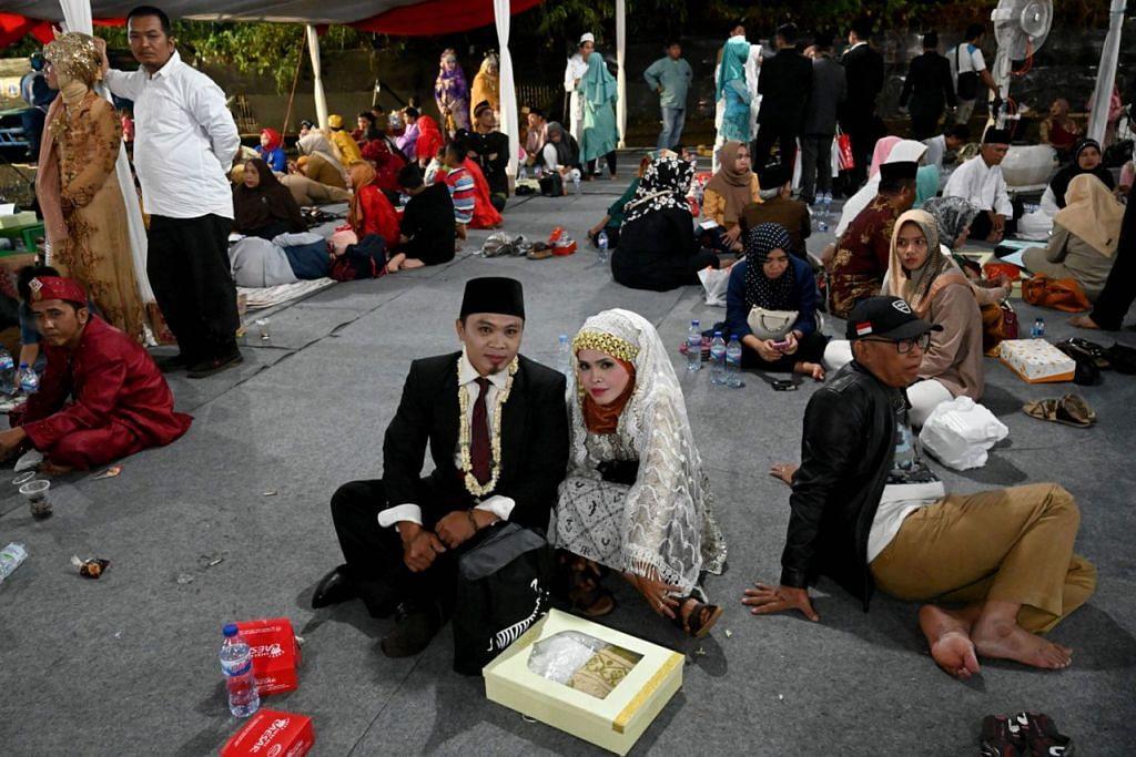 KAHWIN BERAMAI-RAMAI DI INDONESIA -  SAAT GEMBIRA: Sepasang pengantin baru mengambil gambar selepas mereka menyertai lebih 500 pasangan lain yang menjalani acara akad nikah beramai-ramai di Jakarta pada malam Tahun Baru. Acara itu dianjurkan pemerintah Indonesia bagi penduduk miskin dan yang tidak mempunyai dokumen rasmi.  - Foto AFP