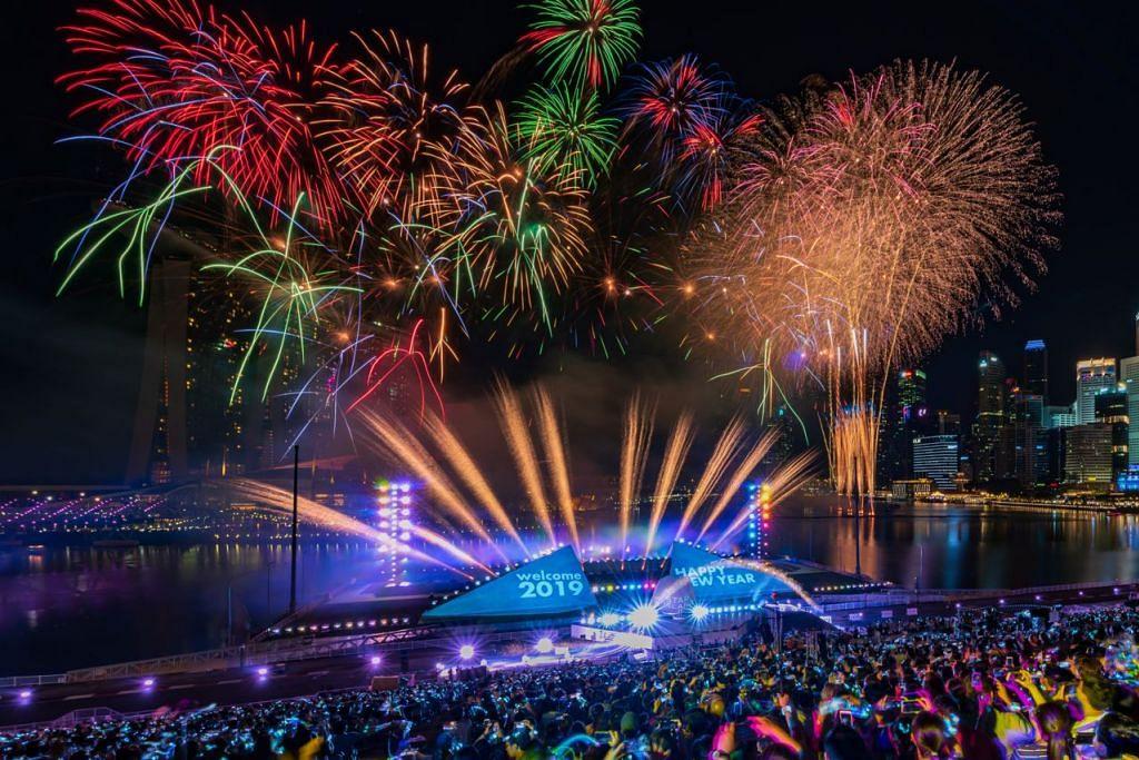 BUNGA API DI MARINA BAY - PERMULAAN TAHUN 'WARNA-WARNI': Tahun penanda aras bagi Singapura, yang bakal meraikan ulang tahun ke-200 atau 'bicentennial', bermula dengan penuh gah apabila ribuan berhimpun di Marina Bay untuk menyertai pesta besar-besaran di sana. Hujan renyai dan cuaca mendung tidak melunturkan kemeriahan peserta, yang sebahagiannya kekal di sana untuk berpesta semalaman. - Foto SPH