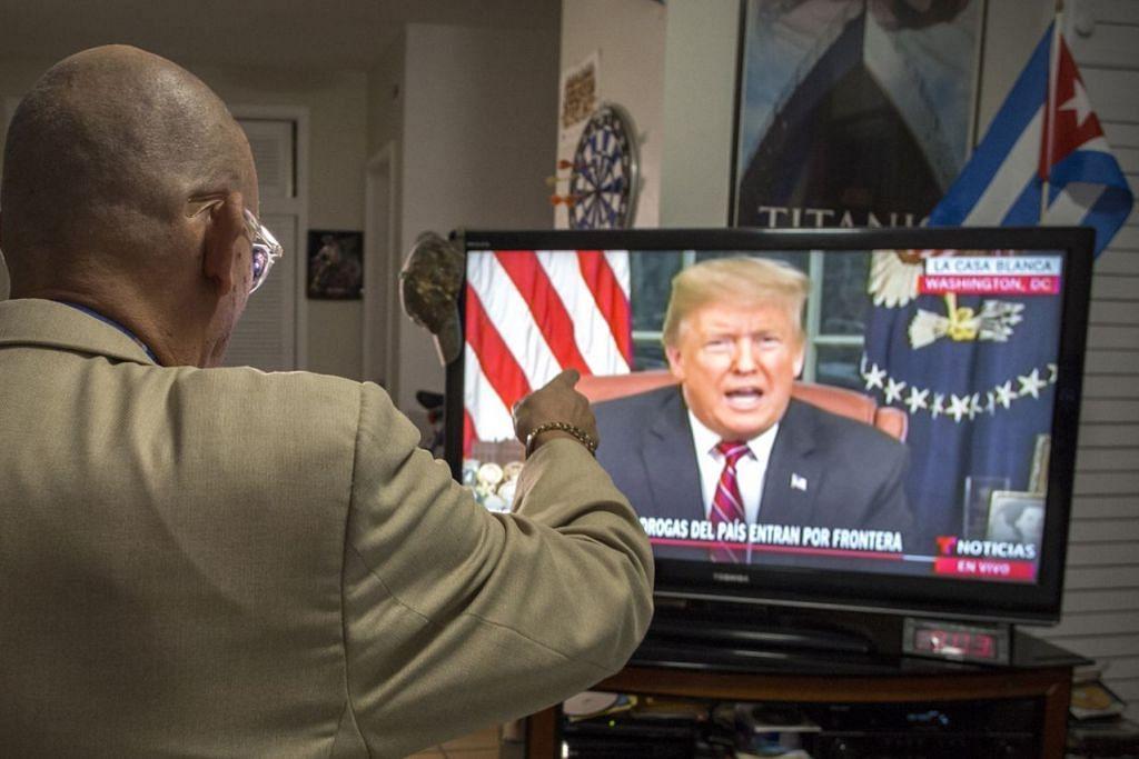GESA RAKYAT SOKONG PEMBINAAN TEMBOK DI SEMPADAN: Encik Oswaldo Hernandez menonton ucapan Presiden Donald Trump kepada seluruh negara dari Pejabat Oval. - Foto EPA-EFE