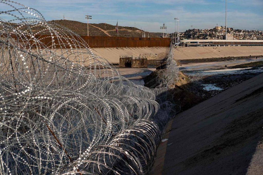 PUNCA ISU: Pagar dawai di sempadan Amerika-Mexico di Sungai Tijuana di negeri Baja California. Presiden Trump mahu membina tembok konkrit bagi menghalang pendatang haram, seperti rakyat Hondura ini, yang memanjat pagar di sempadan itu pada 6 Januari lalu ini untuk memasuki Amerika. - Foto AFP