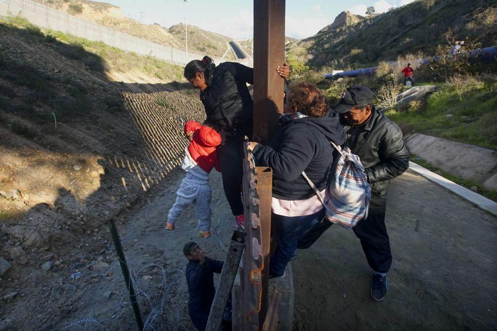 PUNCA ISU: Pagar dawai di sempadan Amerika-Mexico di Sungai Tijuana di negeri Baja California. Presiden Trump mahu membina tembok konkrit bagi menghalang pendatang haram, seperti rakyat Hondura ini (atas), yang memanjat pagar di sempadan itu pada 6 Januari lalu ini untuk memasuki Amerika. - Foto AFP
