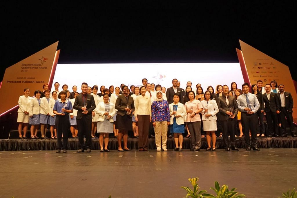 PENGIKTIRAFAN ATAS PERKHIDMATAN: Presiden Halimah Yacob (barisan depan enam dari kiri) telah menyampaikan anugerah kepada penerima Anugerah Perkhidmatan Kesihatan Bermutu (Health Quality Service) Singapura di Pusat Kebudayaan Universiti (UCC), Universiti Nasional Singapura (NUS), semalam. - Foto SINGHEALTH
