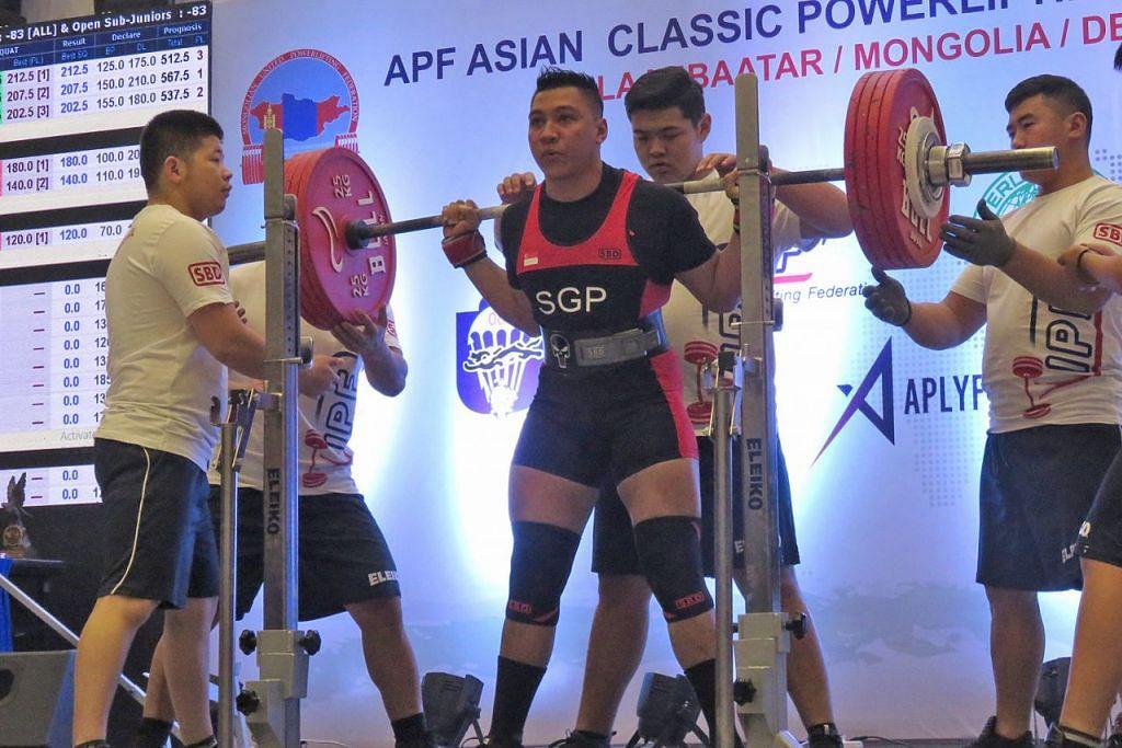 PENGARUH AYAH: Encik Norfatris (tengah) sertai bidang angkat berat selepas sekian lama terlibat dalam bina badan. - Foto MITCHELL LIM