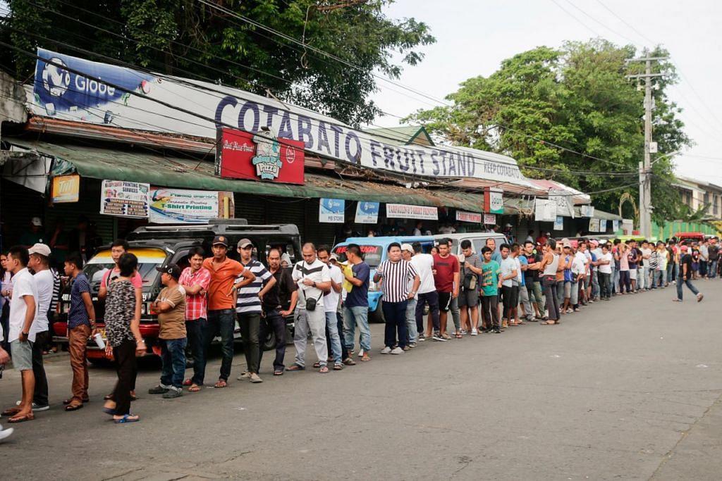 PERKEMBANGAN YANG DINANTIKAN: Penduduk di bandar Cotabato, selatan Filipina, beratur untuk mengundi dalam pungutan suara semalam.- Foto EPA-EFE
