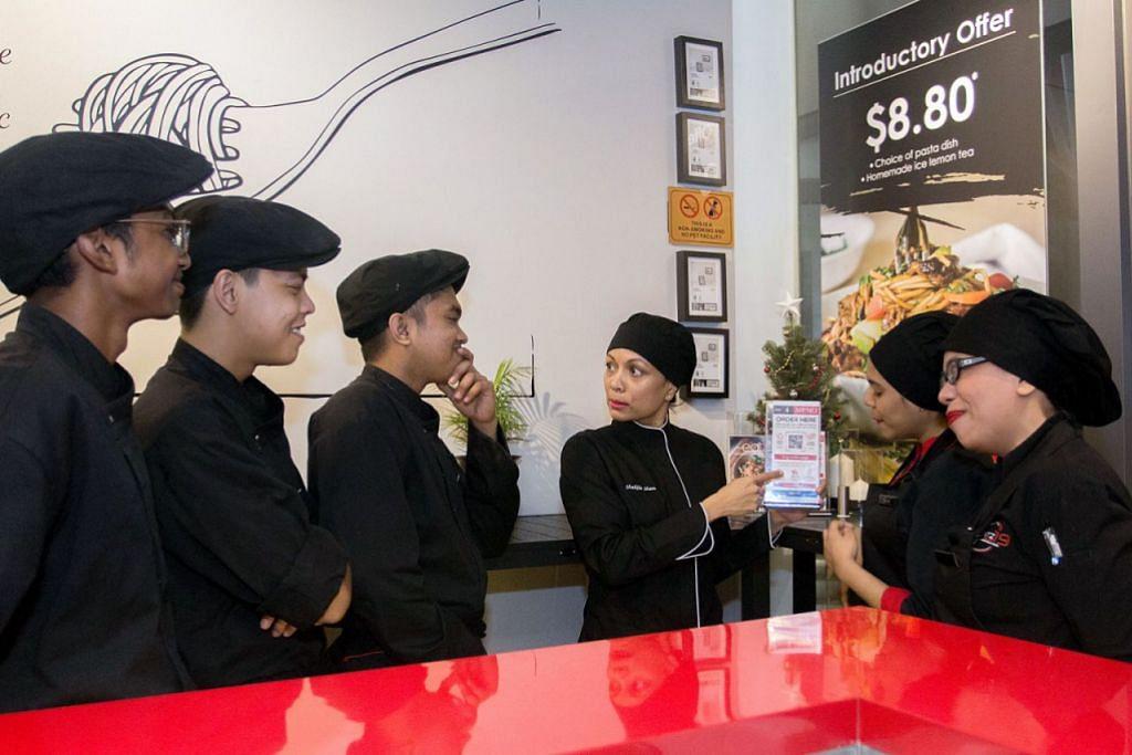 SOKONGAN DIPERLUAS: Pemilik kafe fusion Eatz 19, Cik Shakila Mohd Sham (dua dari kanan)  telah memanfaatkan Program Go Digital SME kelolaan Penguasa Pembangunan Media Infokom (IMDA). - Foto Fail