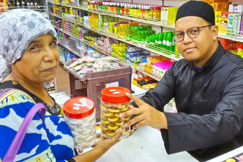 SAMA-SAMA MERIAHKAN TAHUN BARU CINA: Cik Nabisha Mira Said membeli dua bekas kuih tart nanas dan kuih makmur di kedai al-Nusra di Haig Road. Bersama beliau ialah juruwang kedai tersebut, Encik Muhd Alwardi. – Foto BM oleh SAINI SALLEH