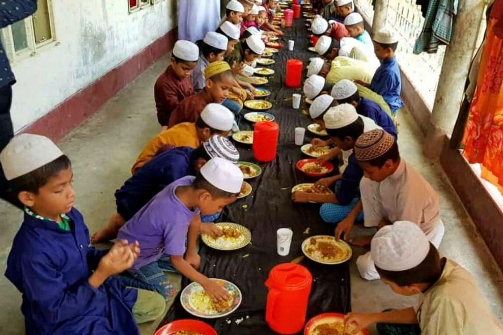 BERSYUKUR DENGAN SESUAP NASI: Anak-anak yatim di sebuah madrasah di Cox's Bazar ini menjamu selera hidangan yang disumbangkan oleh warga Singapura. – Foto FAUZIAH MA'AROF