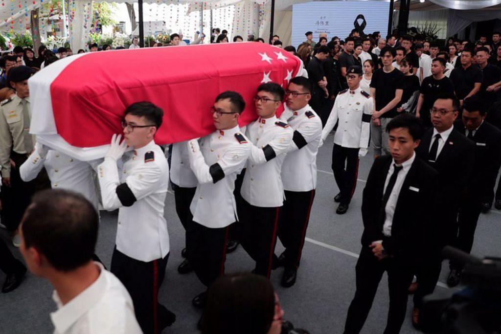 SUASANA PILU: Jenazah Aloysius Pang, yang diberikan penghormatan persemadian tentera, diusung keluar dari lokasi upacara penghormatan terakhir di MacPherson untuk dibawa ke Krematorium Mandai. - Foto BH oleh KELVIN CHNG