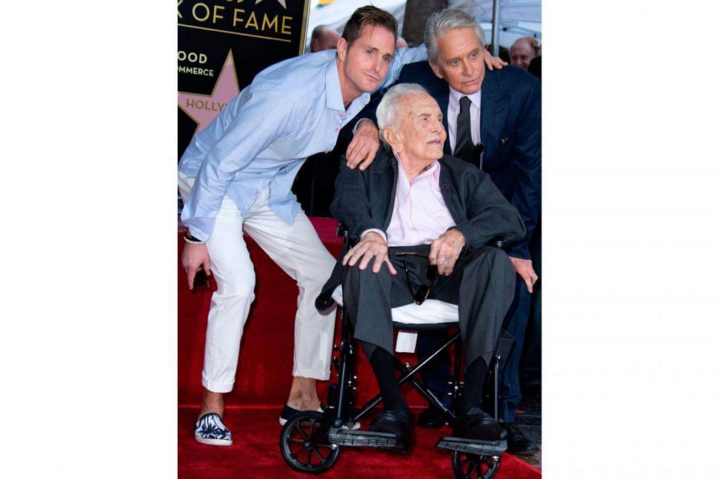 ANTARA TERHEBAT: Kirk Douglas (berkerusi roda) bersama cucunya, Cameron Douglas (kiri) dan anaknya, Michael Douglas (kanan). - Foto AFP