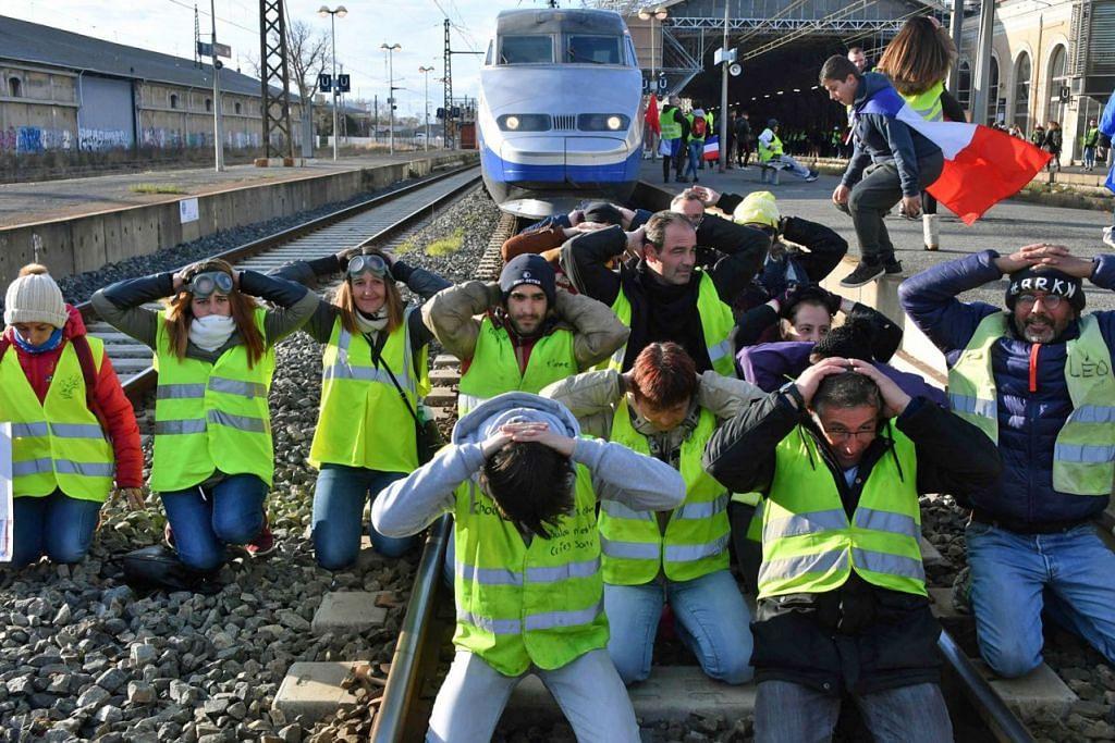 SEKAT LANDASAN: Penunjuk perasaan duduk di landasan di stesen kereta api Beziers, selantan Perancis, pada 19 Januari 2019 - tunjuk perasaan ves kuning pada Sabtu ke-10 berturut-turut.  - Foto AFP