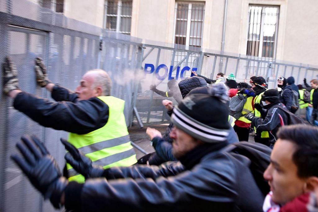 CUBA REMPUH: Penunjuk perasaan cuba memindahkan pintu kawalan rusuhan semasa demonstrasi anti-pemerintah yang dipanggil oleh pergerakan 'Gilets Jaunes' pada 19 Januari 2019 di Nancy, timur laut Perancis.  - Foto AFP