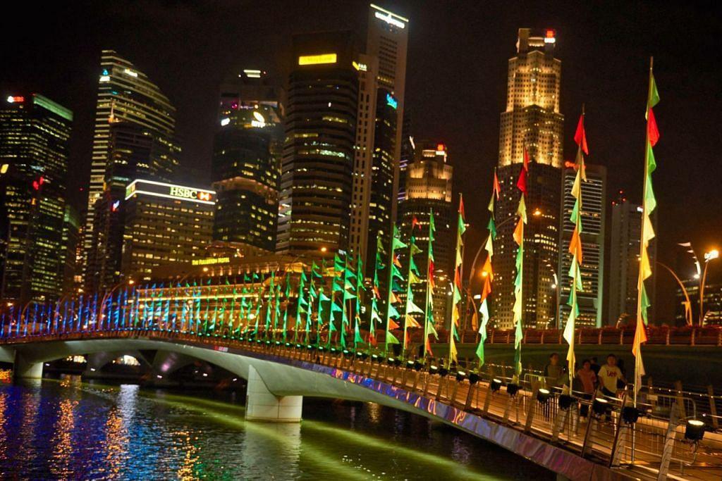 RATUSAN BENDERA DITERANGI LAMPU: Ciptaan seniman Perancis, Encik Sebastien Lefevre, yang diberi nama 'Oriflammes' di Jambatan Jubilee (gambar atas). - Foto VINCENT NG