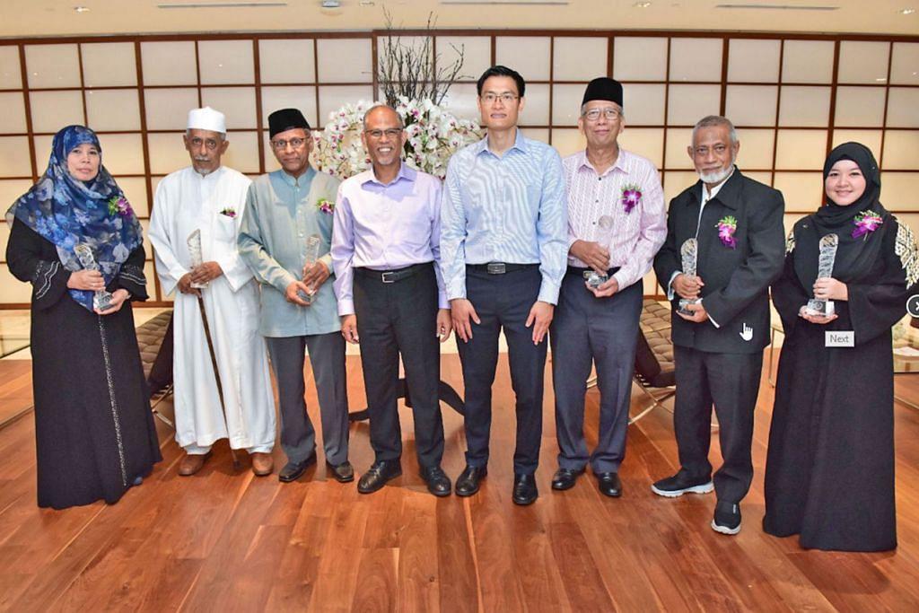JASA DISANJUNG: Encik Masagos (empat dari kiri) dan Encik Esa (lima dari kira) memuji jasa pemimpin masyarakat setempat yang menerima anugerah masing-masing semalam. (Dari kiri) Isteri Allahyarham Ustaz Abdul Halim, Ustazah Masnia Nassim; Syed Abbas Mohamad Alsagoff; Encik Abdullah Mohd Hussain; Encik Mohd Ma'mun HM Fadhlullah; Shaik Hussain Shaik Yacob; dan Cik Wan Nadia Mohamed Yusuf, yang mewakili bapanya Encik Mohamed Yusuf Zuhri. - Foto MUIS