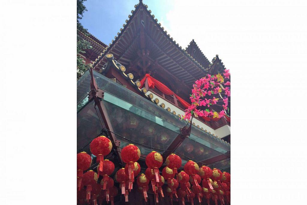 KUIL DIHIAS INDAH: Tanglung digantung dalam barisan kemas di luar Kuil Relik Gigi Buddha (Buddha Tooth Relic Temple) yang terletak di South Bridge Road. Bunga-bunga plastik juga menjadi hiasan di luar kuil tersebut, sesuai dengan Tahun Baru Cina yang juga dikenali sebagai Perayaan Musim Bunga. - Foto NUR FATHIN AWALLUDIN
