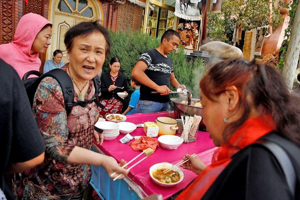 DORONGAN KOMERSIAL: Sekumpulan pelancong menikmati sajian di bandar lama Kashgar di Xinjiang, Kawasan Autonomi Uighur, China yang ramai penduduk Islam. Kebangkitan perkhidmatan dan makanan halal di China telah mencetuskan rasa kurang senang dalam kalangan kaum majoriti Han di China dan mencetus langkah pemerintah China mengawal kebangkitan tersebut. - Foto REUTERS