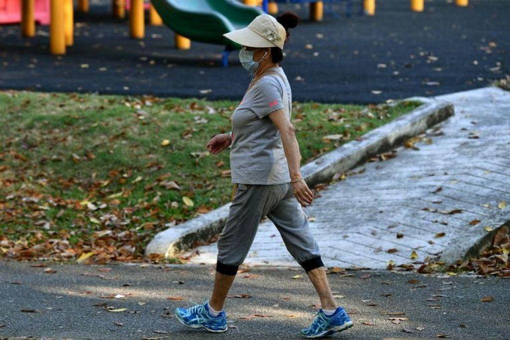 Seorang wanita memakai pelitup muka semasa berjalan di Taman Tampines Central.