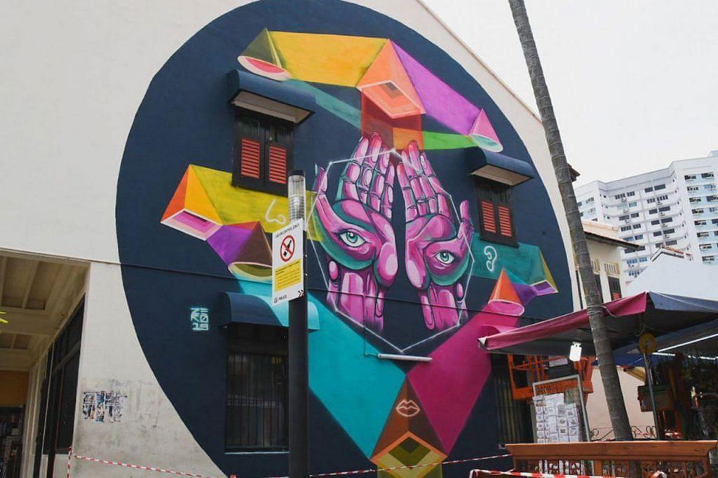 CORAK GEOMETRIK: Encik Mohammed Zulkarnaen Othman menghiasi dinding rumah kedai sekitar Kerbau Road ini dengan lukisan yang melambangkan warna-warni rempah ratus yang dijual di Little India. - Foto ZUL ZERO