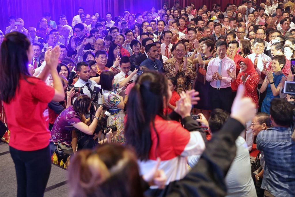 SALING BERKONGSI KEGEMBIRAAN: Presiden Halimah bersama-sama meraikan majlis sambutan Tahun Baru Cina di Pusat Kebudayaan Cina Singapura (SCCC), yang turut dihadiri beberapa anggota Kabinet, wakil persatuan suku kaum Cina, serta wakil masyarakat lain.  - Foto BH oleh KEVIN LIM