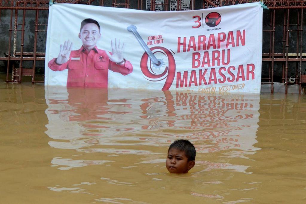 CABARAN DAN HARAPAN: Seorang budak lelaki berenang di kawasan kediaman berikutan banjir di Makassar, Sulawesi Selatan, Indonesia, dengan berlatar belakang sepanduk 'Harapan baru Makassar'. - Foto REUTERS