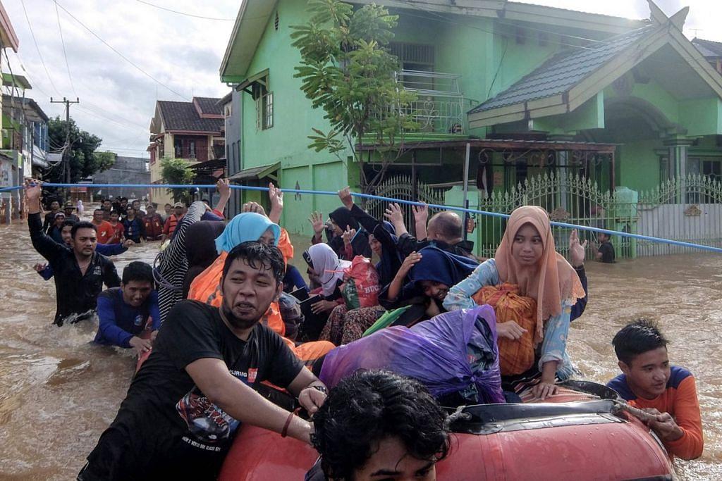 TINGGALKAN RUMAH: Para penduduk mengosongkan rumah mereka di Makassar menyusuli hujan lebat dan angin kencang yang melanda bahagian selatan pulau Sulawesi, menyebabkan air sungai melimpahi tebing membanjiri kawasan di sembilan daerah selatan. Banjir kilat dan tanah runtuh yang berlaku pada hujung bulan lalu itu mengakibatkan puluhan orang terkorban dan ramai terpaksa berpindah. - Foto AFP