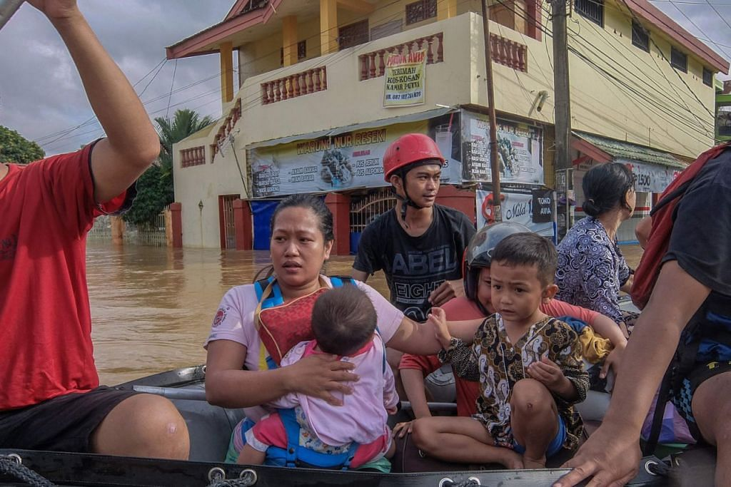 SELAMATKAN KELUARGA: Wanita bersama anak kecil ini dibantu mencari perlindungan di tempat lebih selamat. - Foto AFP