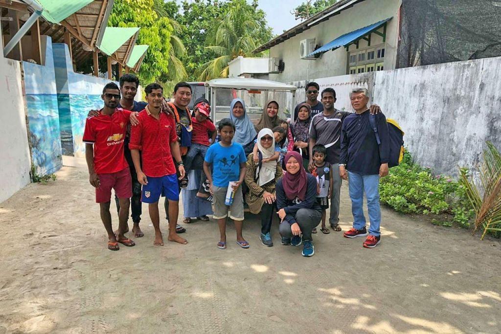 JALIN HUBUNGAN: Sepanjang percutian di Maldives, penulis (depan bertudung merah gelap) bersama keluarga menjalani kehidupan orang Maldives dan berpeluang berinteraksi dengan mereka. Mereka mengendali rumah tamu (berdinding biru) tempat penulis serta keluarga menginap. - Foto BH oleh NUR HUMAIRA SAJAT