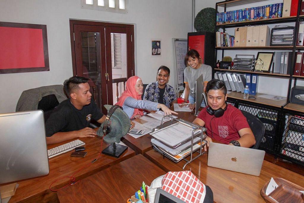 UTAMAKAN PEKERJA SETEMPAT: Encik Mustaffa (tengah) berusaha mewujudkan budaya kerja yang menarik dan memenuhi keperluan pekerja Singapura, sebagai usaha tidak bergantung kepada pekerja asing. - Foto BH oleh IQBAL FAIZAL