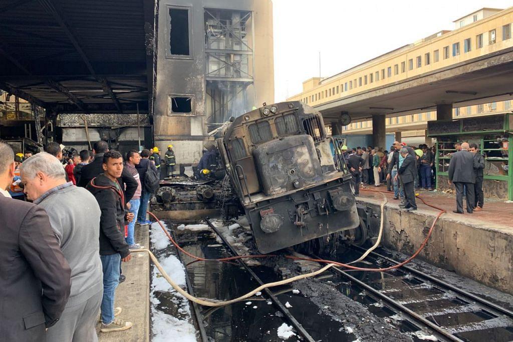 TERBAKAR SELEPAS LANGGAR PENGADANG: Tren yang tergelincir lalu melanggar pengadang di stesen Ramses Rabu lalu kelihatan terbiar di landasan. Nahas tren disifatkan sebagai perkara biasa di Mesir. - Foto EPA-EFE