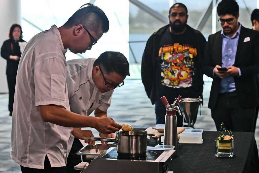 HIDANGAN UNIK: Pengarah Kulinari Rasel Catering Singapore Encik Teo Yeow Siang dan Cef Boey Min Hwa (kiri) memberi demonstrasi masakan 'high fashion' halal kepada para hadirin semasa satu acara yang diadakan di Gardens by the Bay baru-baru ini. - Foto BH oleh DESMOND FOO
