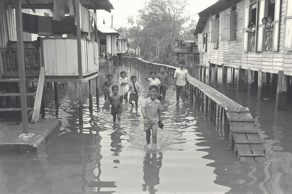 SUDAH BIASA DENGAN AIR: Kanak-kanak di Kampung Sungei Mandai Kechil, sudah terbiasa dengan air laut yang pasang dan banjir dan tidak kekok bermain dan berjalan walaupun dalam suasana perayaan seperti majlis keramaian dan Hari Raya. - Foto fail.