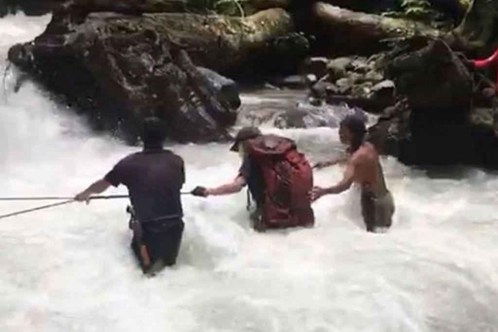 LINTAS SUNGAI ARUS DERAS: Penulis dan anaknya perlu melintasi sungai deras dengan bantuan pemandu orang setempat.  - Foto ihsan ZAIDI YACOB