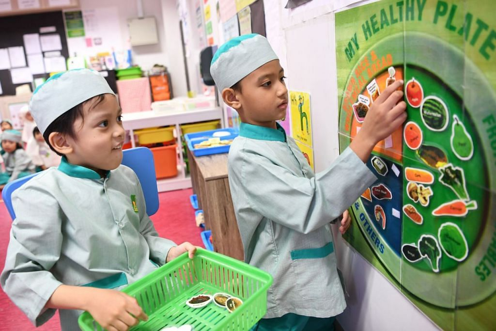 KENALI GAYA PEMAKANAN SIHAT: Pelajar berumur enam tahun, Aydin Mikhail Mohamad Ashik (kiri) dan Azaan Khan Mohamed Rafi Khan, melakukan kegiatan melibatkan konsep panduan 'My Healthy Plate' HPB.  - Foto BH oleh KHALID BABA