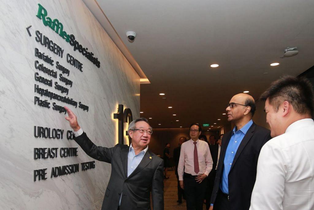 DENGAR TAKLIMAT: Encik Tharman Shanmugaratnam (tengah) mendengar taklimat daripada Pengerusi Eksekutif Raffles Medical Group, Dr Loo Choon Yong, mengenai Pusat Pakar Raffles yang dirasmikan semalam. - Foto ZAOBAO