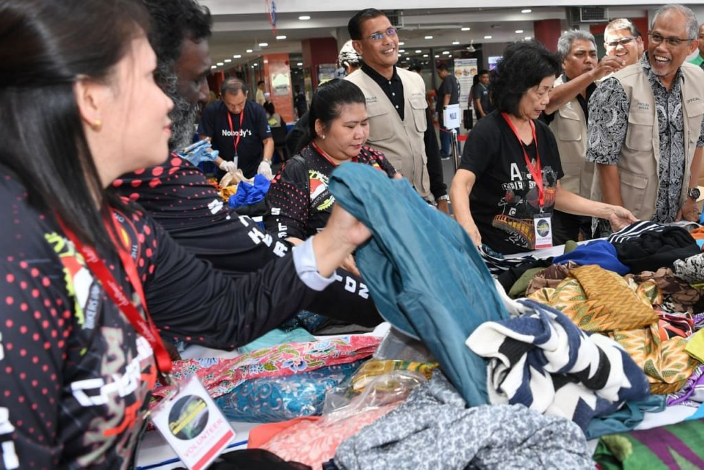 SAMA-SAMA MEMBANTU: Encik Masagos (kanan) berinteraksi dengan para relawan yang sibuk mengumpulkan dan melipat pakaian yang didermakan orang ramai untuk Projek Ihsan 2019 di Kelab Masyarakat Tampines West semalam. - Foto BH oleh KHALID BABA.