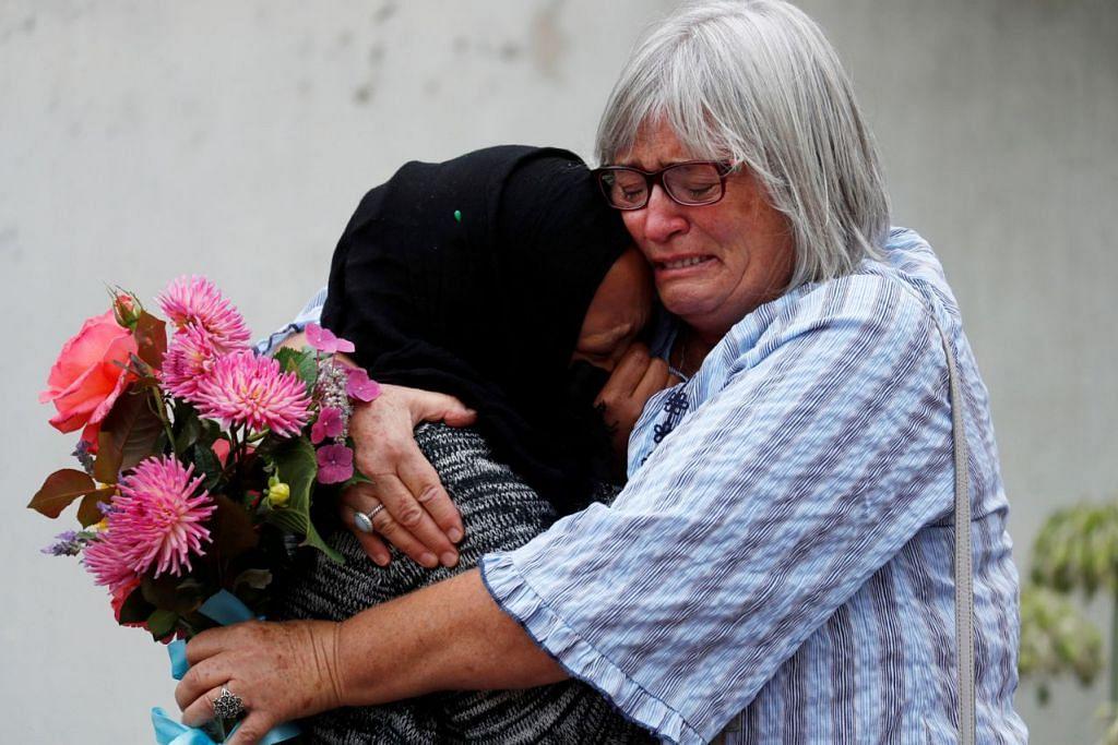 TAHAN SEBAK: Dua wanita tidak dapat menahan sebak dan berpelukan dekat Masjid Al Noor, Christchurch, New Zealand, semalam. - Foto REUTERS