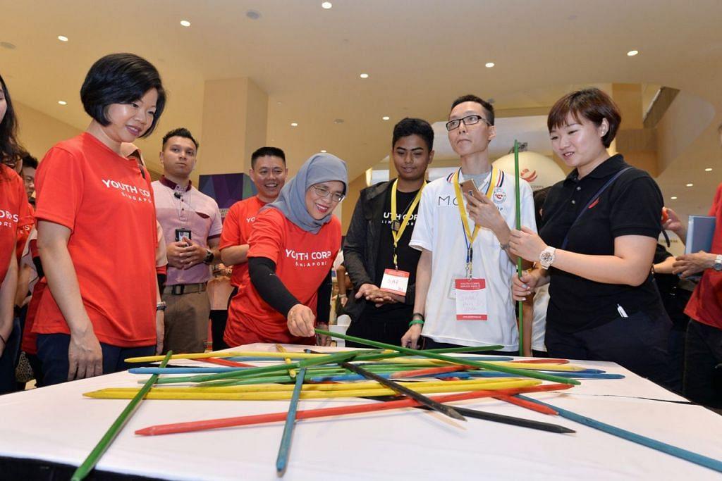 CUBA PERMAINAN: Presiden Halimah Yacob (empat dari kanan) menyertai aktiviti dengan sukarelawan belia di pelancaran Minggu Khidmat Kor Belia Singapura. - Foto NYC
