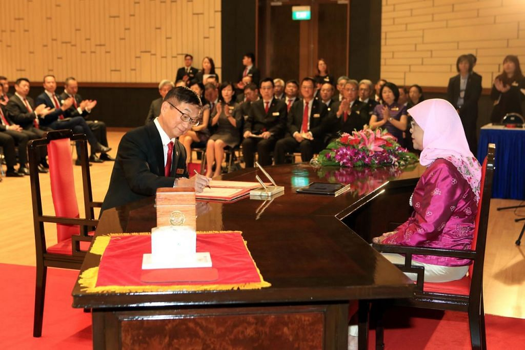 PIMPIN MASYARAKAT PENIAGA CINA: Presiden Halimah Yacob sedang menyaksikan Encik Roland Ng menandatangani surat perlantikannya sebagai Presiden Dewan Perniagaan dan Perusahaan Cina Singapura (SCCCI) bagi penggal kedua, dalam majlis perlantikan Majlis SCCCI yang ke-60 baru-baru ini. - Foto WANBAO