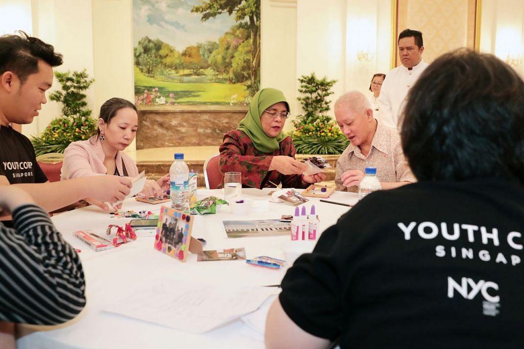 BUAT KEGIATAN KRAF BERSAMA: Presiden Halimah Yacob (tengah) melakukan aktiviti seni bersama pesakit Institut Kesihatan Mental (IMH) dan sukarelawan dari Kor Belia Singapura (YCS) di Istana semalam. - Foto BH oleh KELVIN CHNG